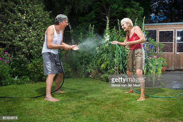 Mature couple spraying eachother with gardenhose.