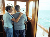 Mature couple standing at helm of boat, steering, rear view