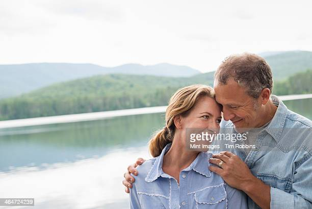 A mature couple standing by a lake shore.
