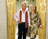 Mature couple standing by curtained doorway, portrait