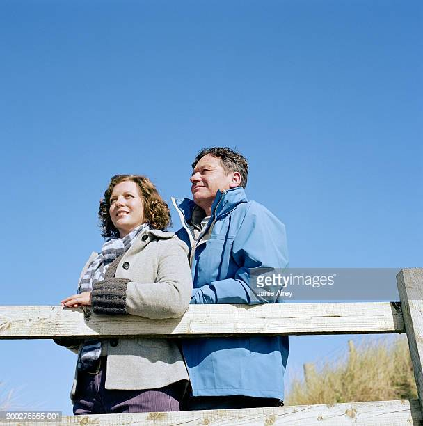 Mature couple standing by wooden rail outdoors, low angle view
