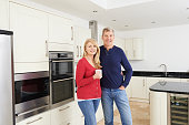Mature Couple Standing In Beautiful Fitted Kitchen Together