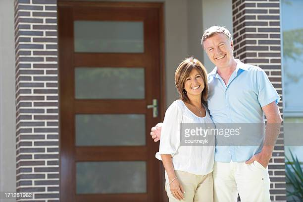 Mature couple standing in front of a modern house