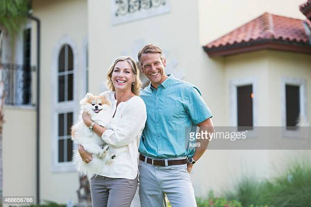 Mature couple standing in front of their mansion