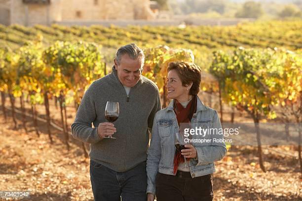 Coppia matura in piedi in vineyard, che tiene i bicchieri di vino, smi