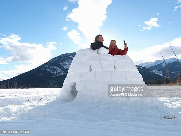 Mature couple standing inside igloo photographing themselves with mobile phone