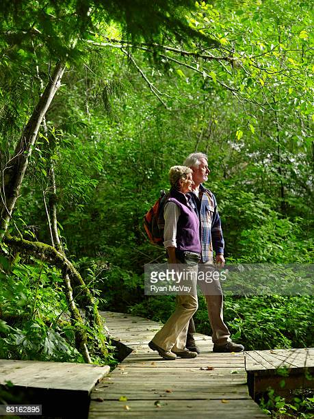Mature couple standing on pathway in forest.