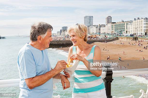 Mature couple standing on pier eating chips.