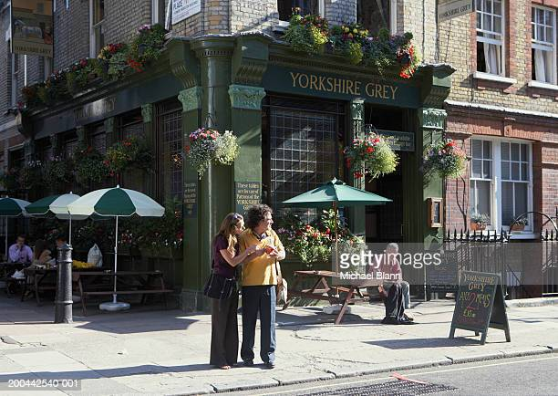 Mature couple standing on street holding guide book, pub in background