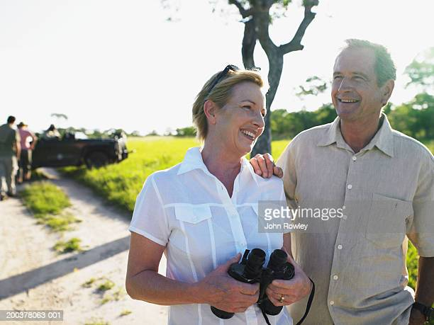 Mature couple standing on track, woman holding binoculars, smiling