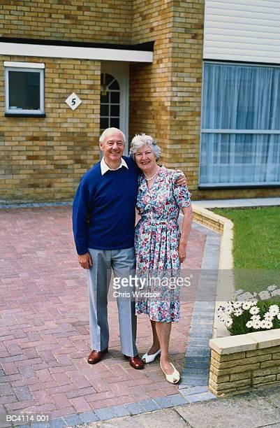 Mature couple standing outside house, portrait