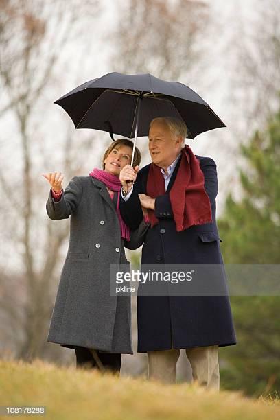 Mature Couple Standing Under Umbrella