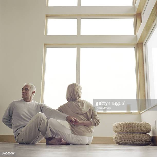 Mature couple stretching together in home