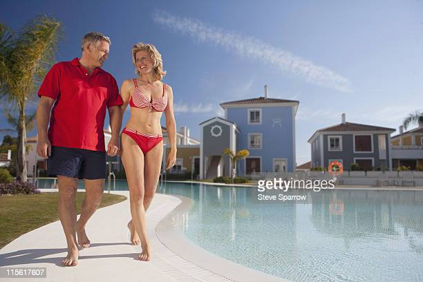 Mature couple strolling by pool