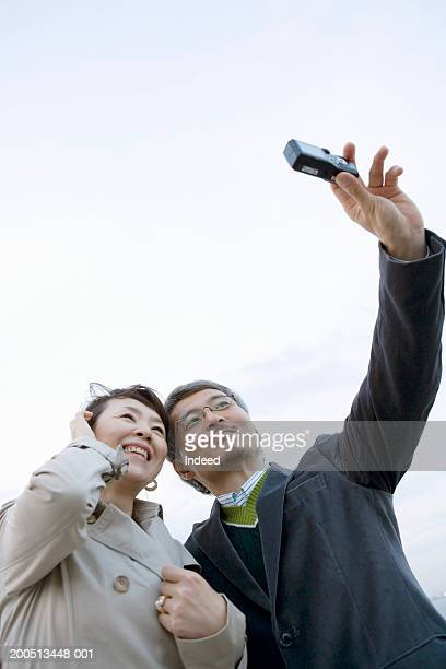 Mature couple taking self portrait, low angle view