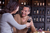 Mature Couple Toasting and Enjoying Themselves Drinking Wine, Focus on Male