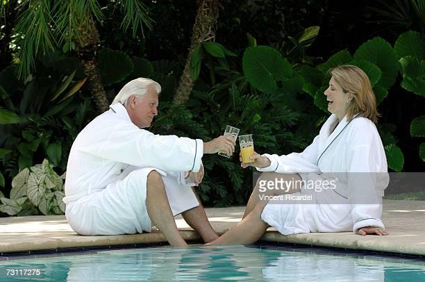 Mature couple toasting orange juice in swimming pool