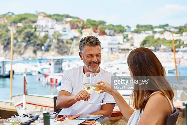 Mature couple toasting wineglasses at restaurant