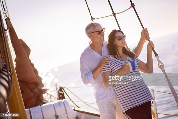 Mature couple travelling on a yacht with early morning coffee
