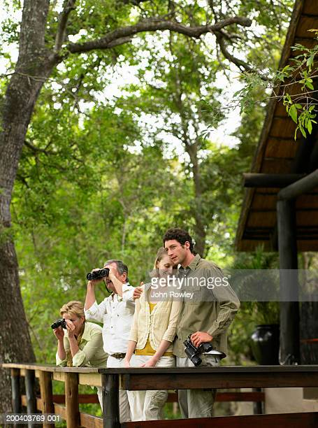 Mature couple using binoculars on balcony by couple embracing