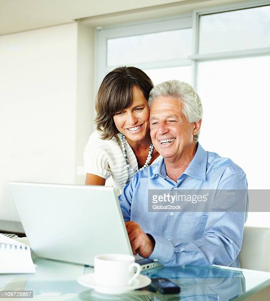 Mature couple using laptop at home and smiling