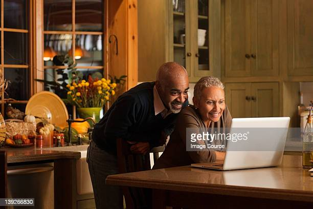 Mature couple using laptop in kitchen