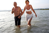 mature couple wading and holding hands