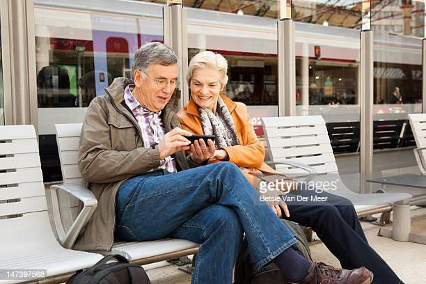 Mature couple waiting for train looking at i phone