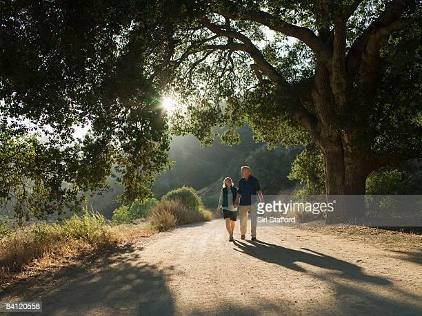 mature couple waking down dirt road