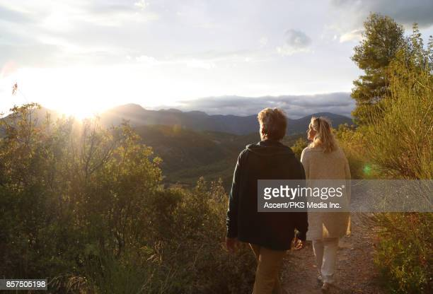 Mature couple walk along mountain slope above valley below