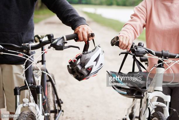 Mature couple walking along rural pathway with bicycles, mid section