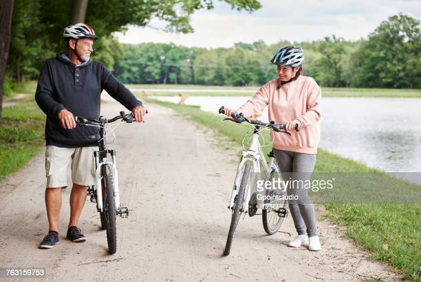 Mature couple walking along rural pathway with bicycles, smiling