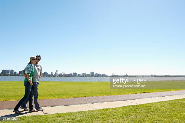 Mature couple walking by river with city in background, Perth, Australia