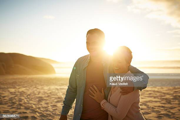 Mature couple walking close together on beach