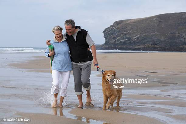 Mature couple walking dog along beach, arms around