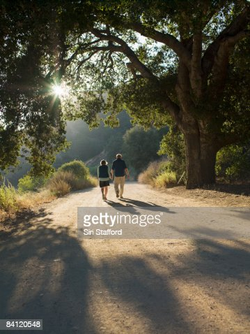 Mature couple walking down dirt road : Stock Photo