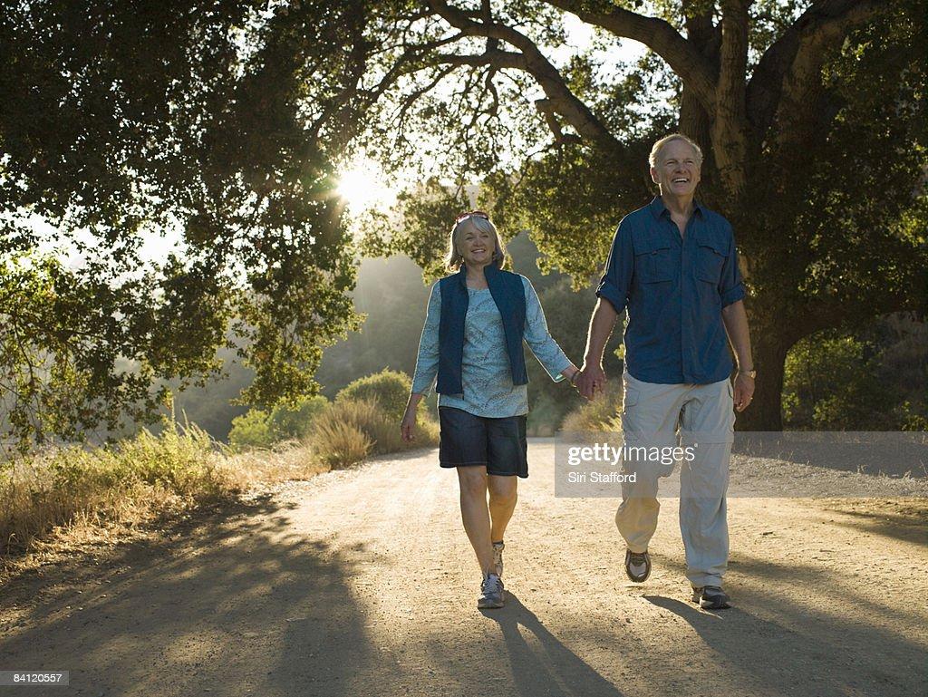 Mature couple walking down dirt road : Stock Photo