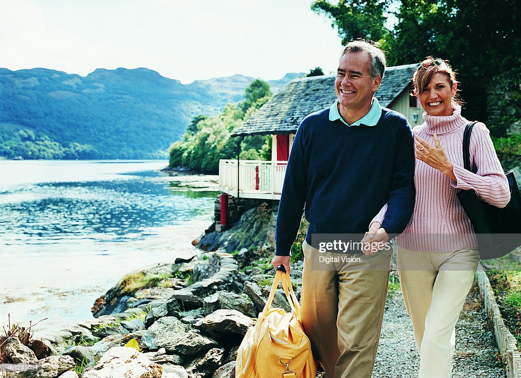 Mature Couple Walking Hand in Hand and Laughing Together Beside a Lake