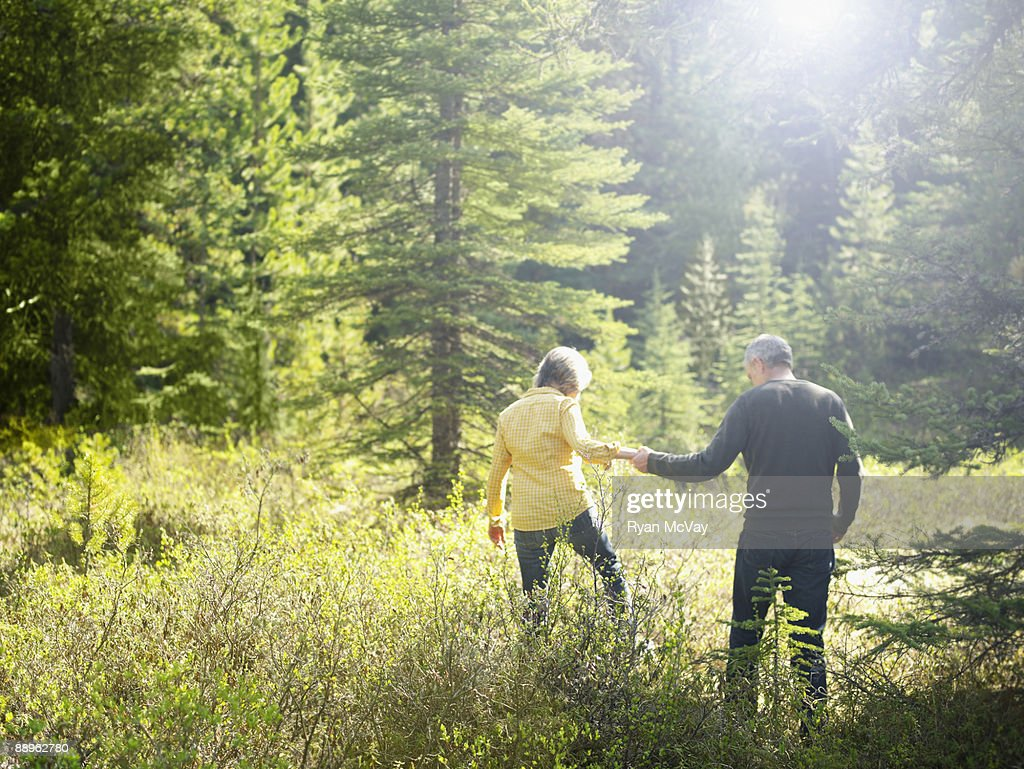 Mature couple walking in forest : Stock Photo