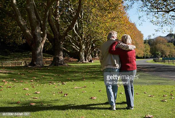 Mature couple walking in park, rear view