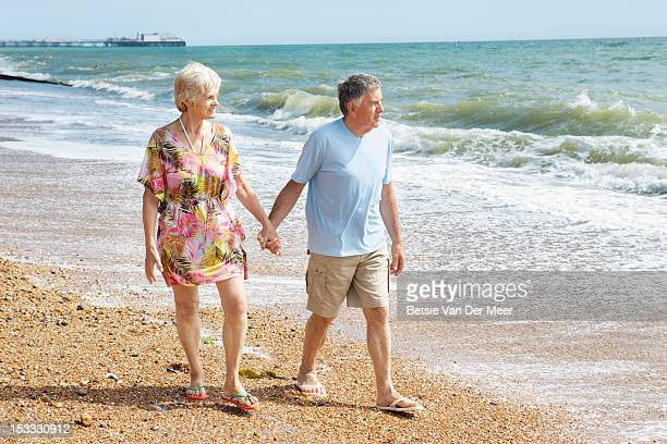 Mature couple walking on beach.