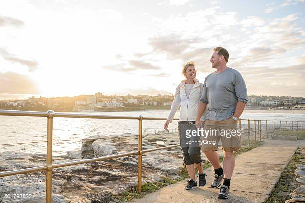 Mature couple walking on boardwalk at sunset, Bondi Beach