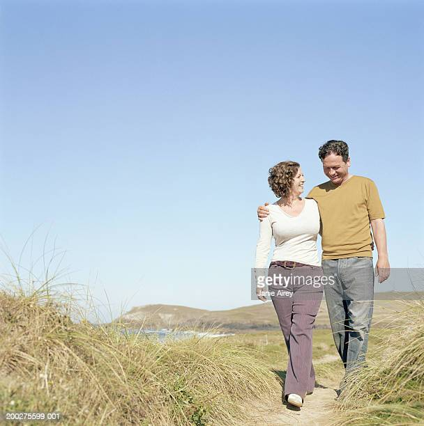 Mature couple walking on path by sea, smiling