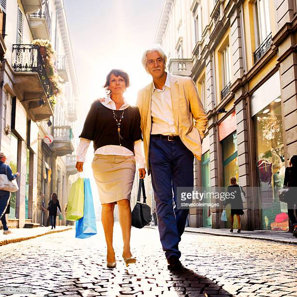 Mature Couple Walking On Street Holding Shopping Bags