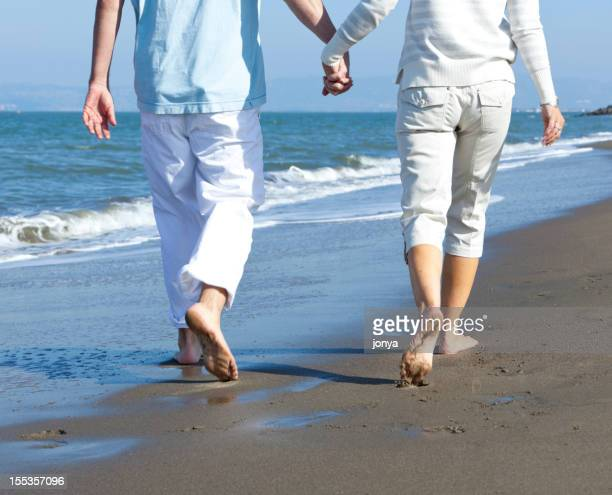 mature couple walking the beach (cropped)