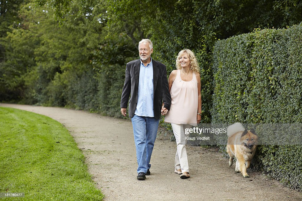 Mature couple walking their dog in the park : Stock Photo