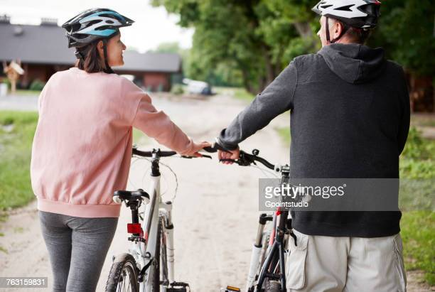 Mature couple walking with bicycles, rear view