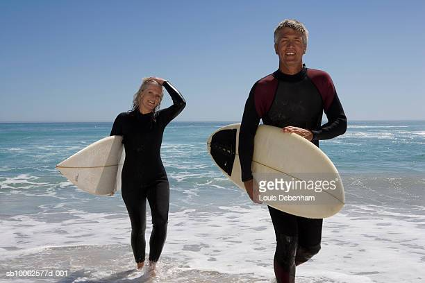 Mature couple walking with surfboards on beach