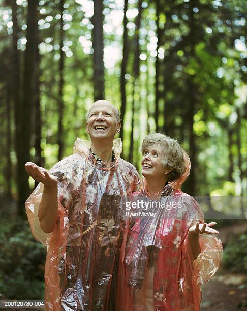 Mature couple wearing raincoats, feeling for raindrops with hands