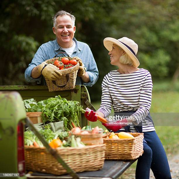 Mature Couple With Baskets Of Harvested Vegetables.